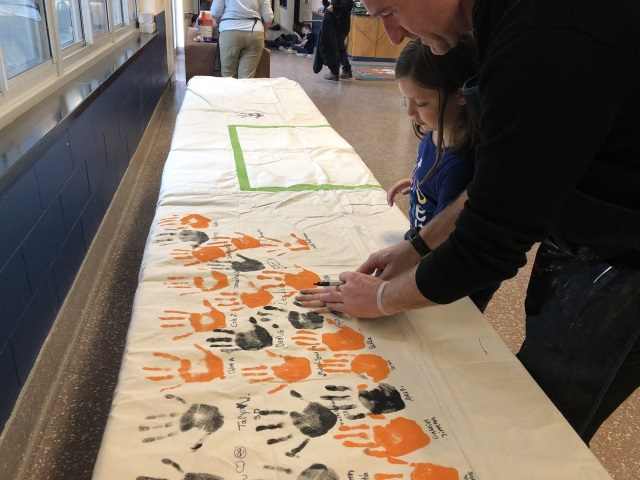 Cottle students make handprint pledges to be kind on a banner.