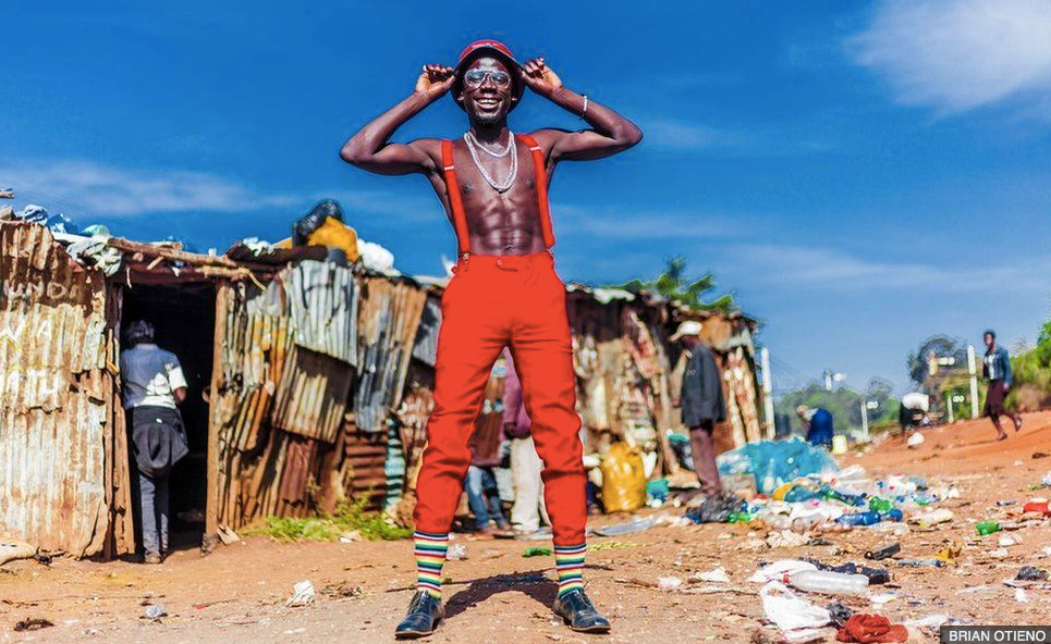 Photo of man in red pants, red suspenders, bare-chested in front of residential shack in Kibera, Kenya.  From Kibera fundraiser photo collection.