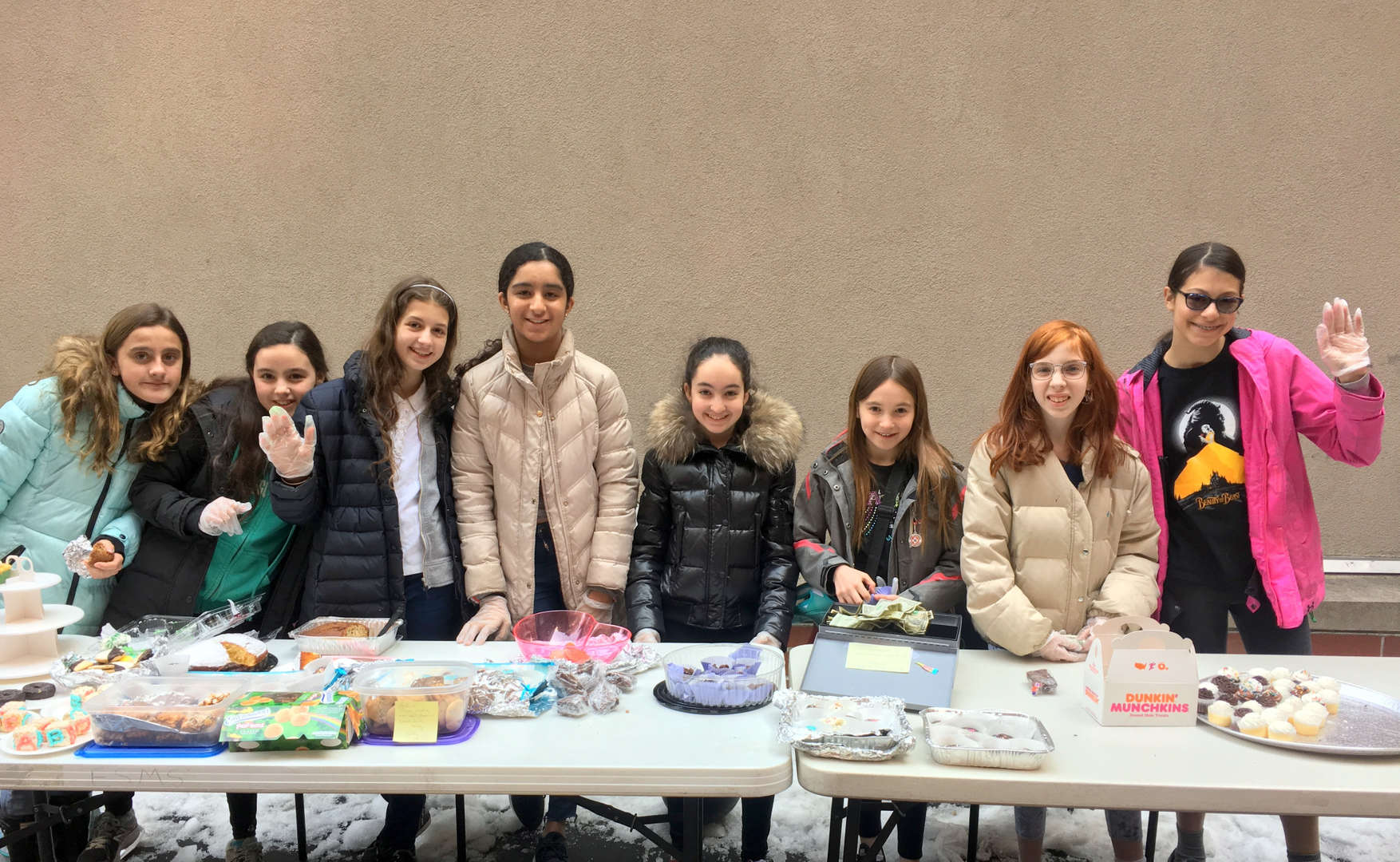 Students manning the bake sale table outdoors