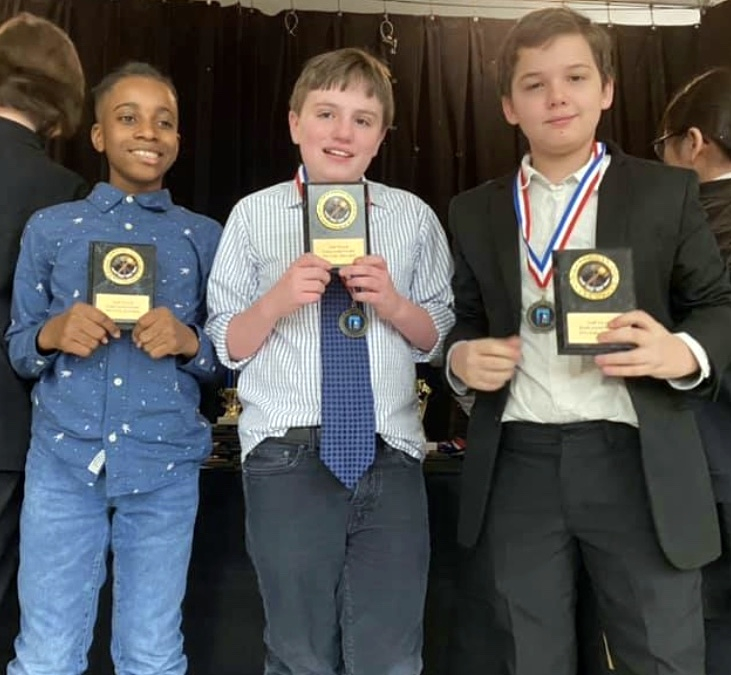 Three ESMS students (three boys) with debate team awards