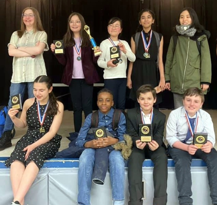 Several ESMS students on stage with debate team awards