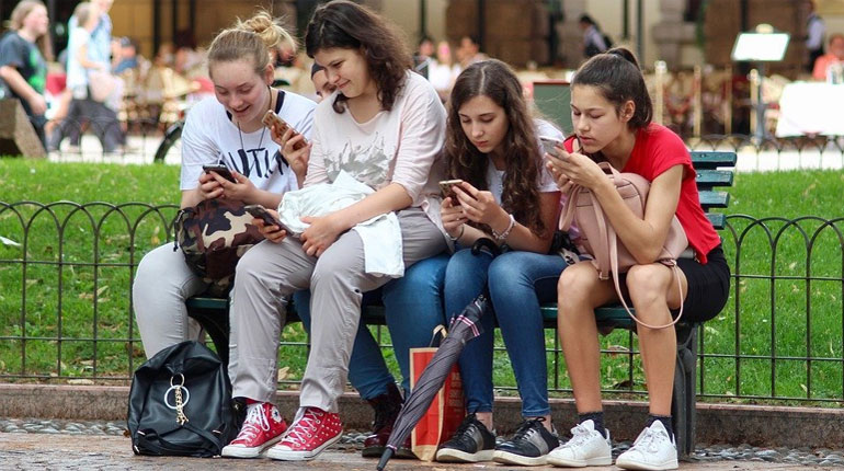 A photo of five teenager sitting on a park bench, staring at their respective cell phones.  This photo relates to our 6th grade advisory program on Privacy and Balancing Technology Use.
