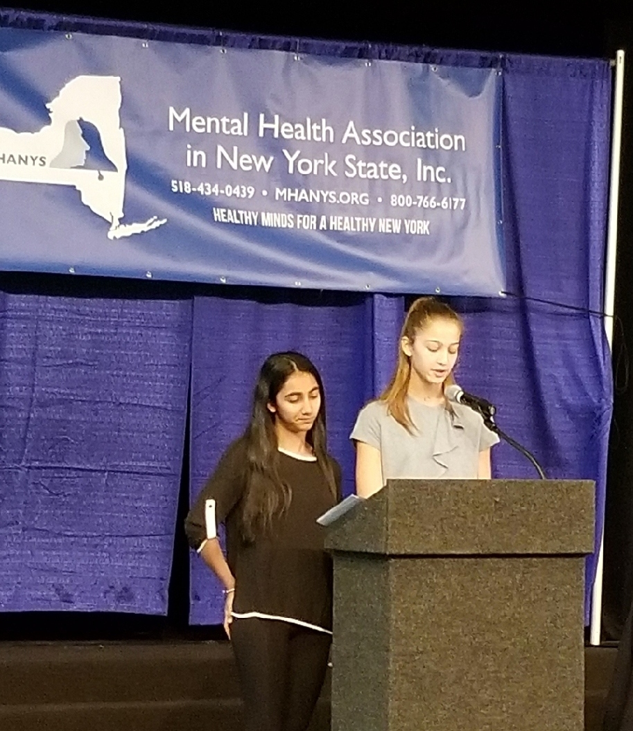 A photo of two students presenting at a NYS Mental Health symposium