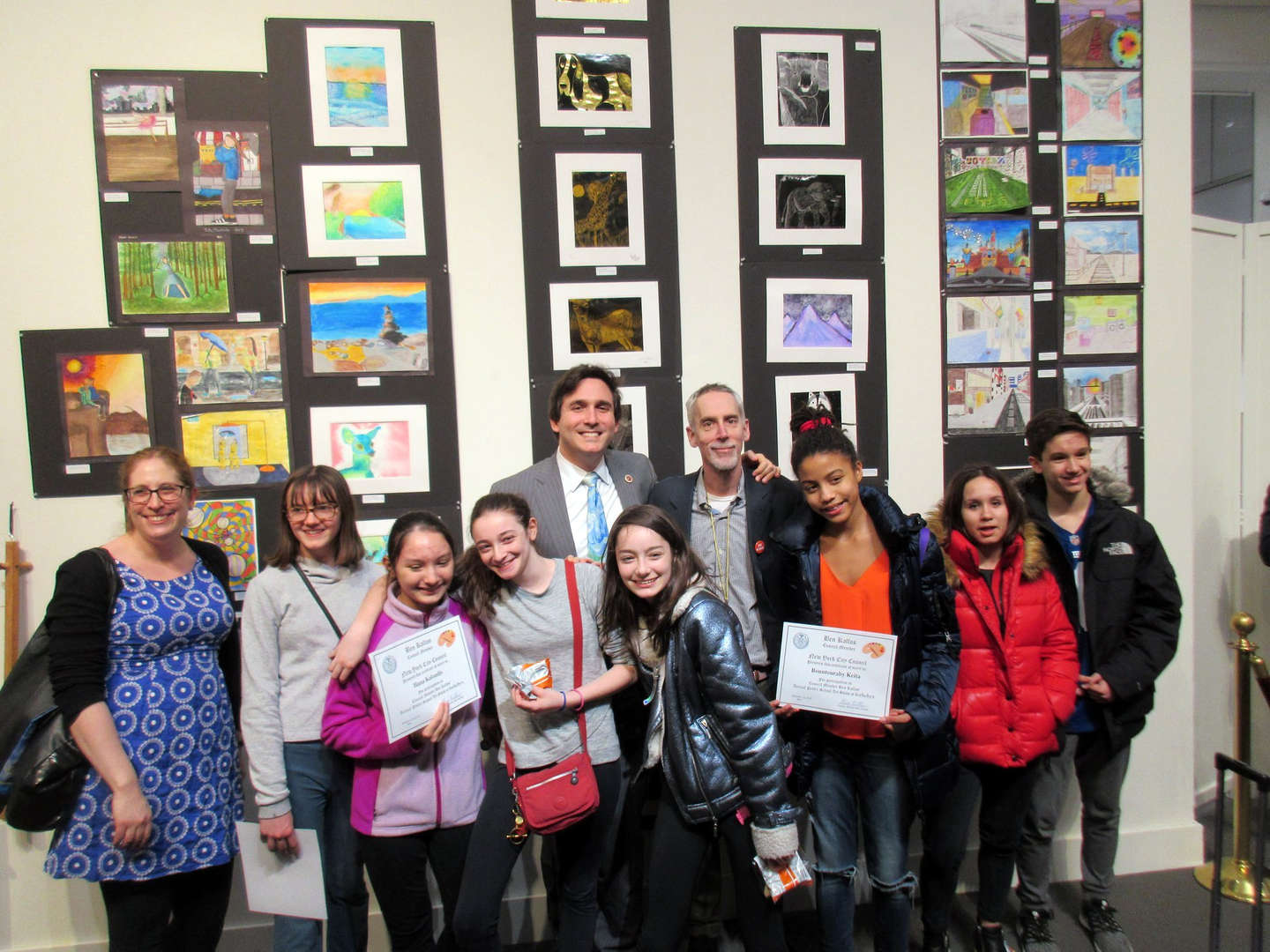 Photo of Principal Getz, Councilman Ben Kallos, and some ESMS students in front of student art at the Sotheby's student art show