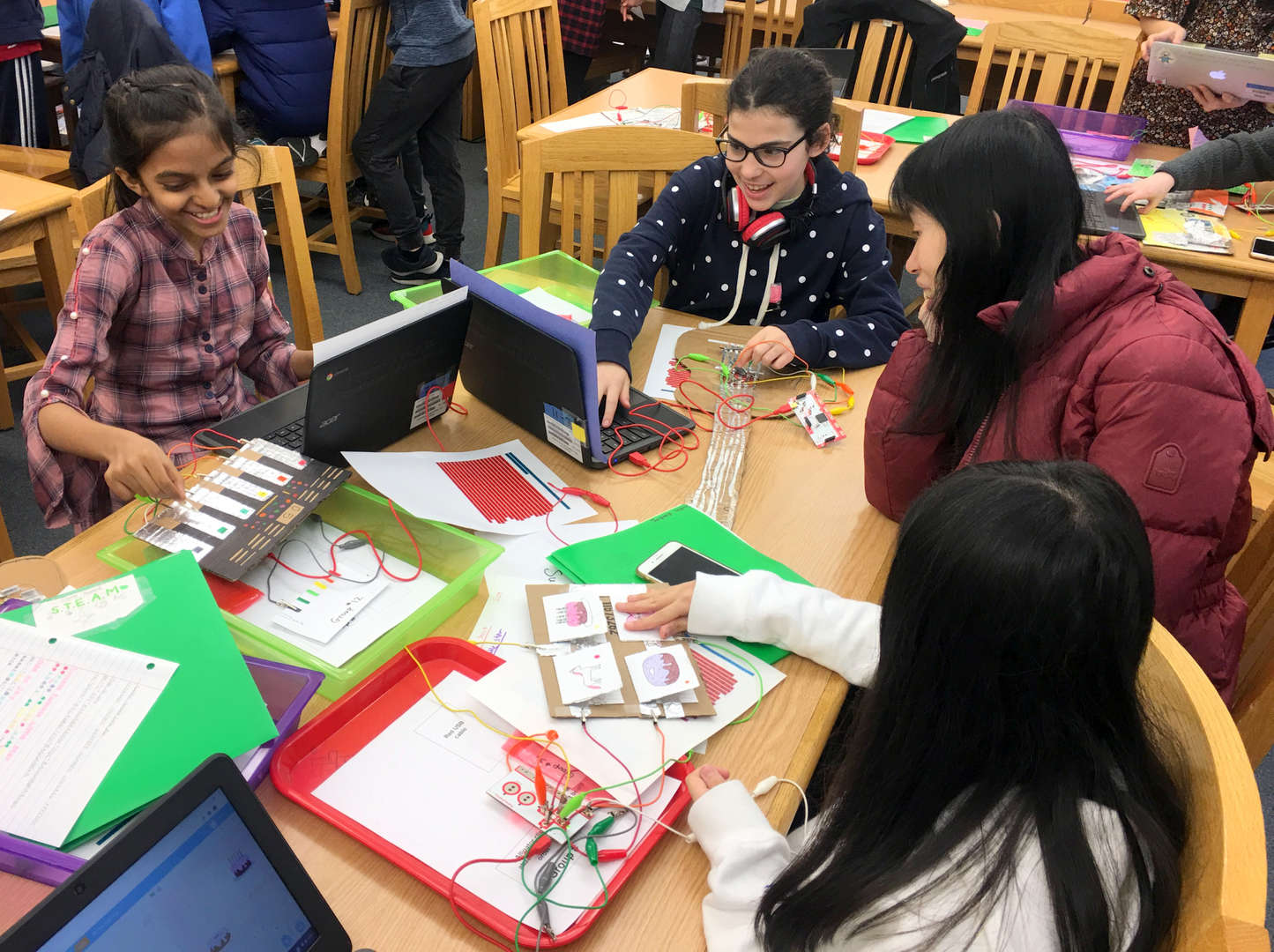 Photo of three students presenting their STEAM Science projects to a parent, all sitting around a table
