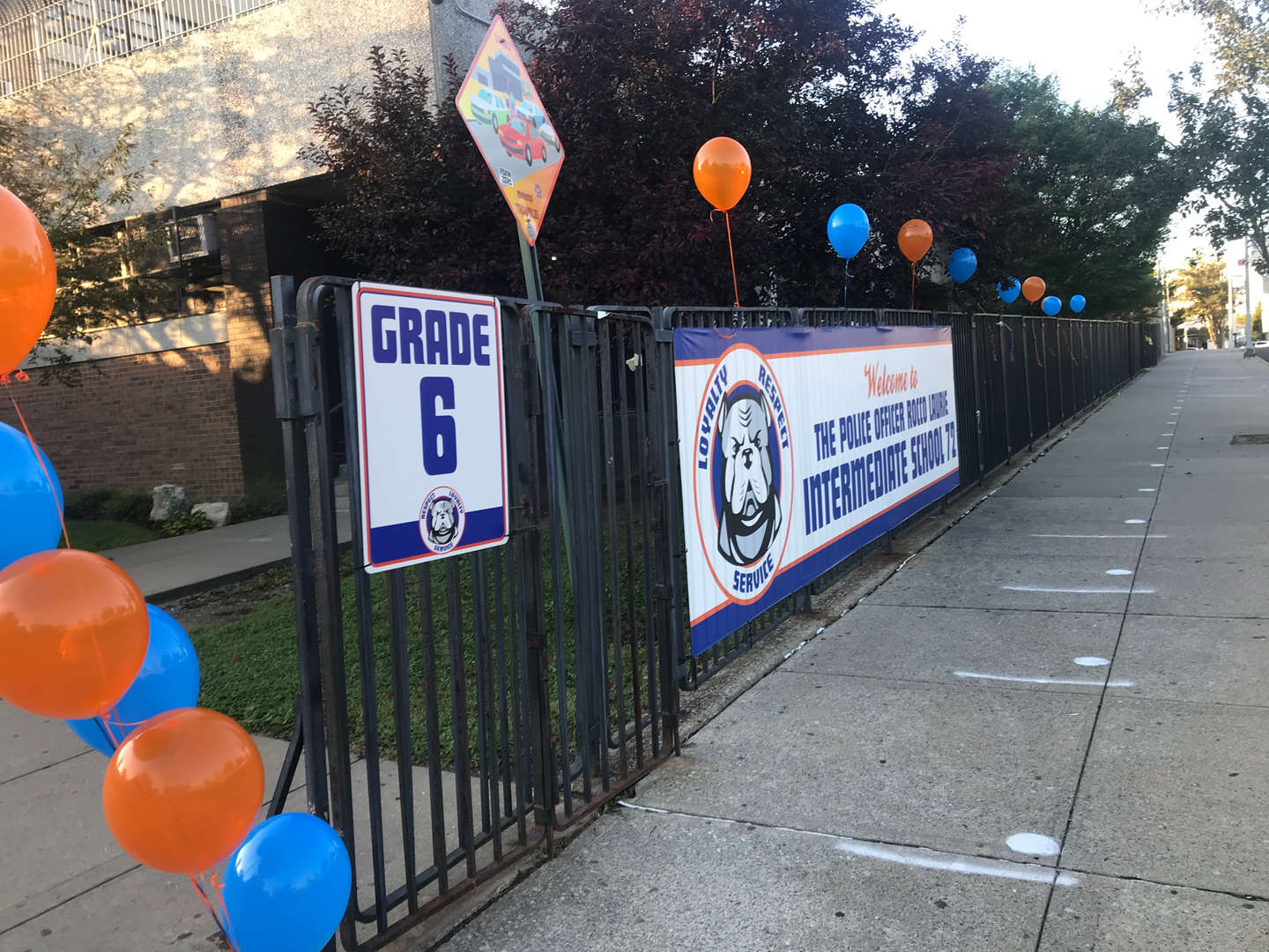 Banner and balloons on fence in front of IS72
