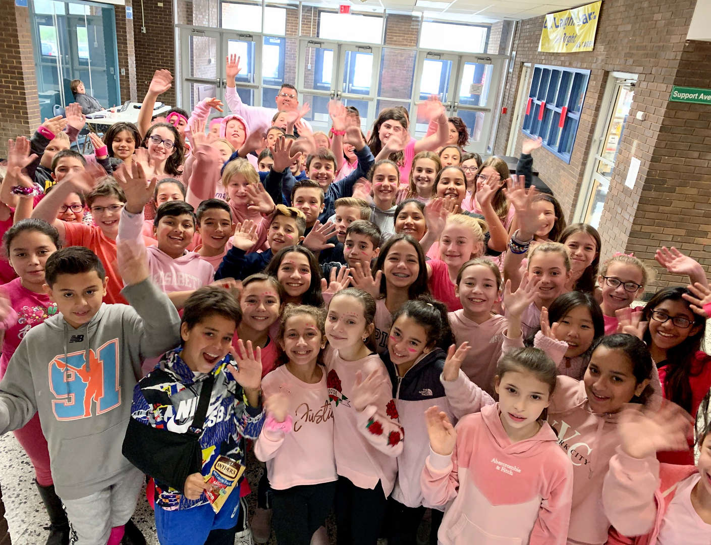 Principal Tom Cozzocrea gather in the school lobby dressed in pink.