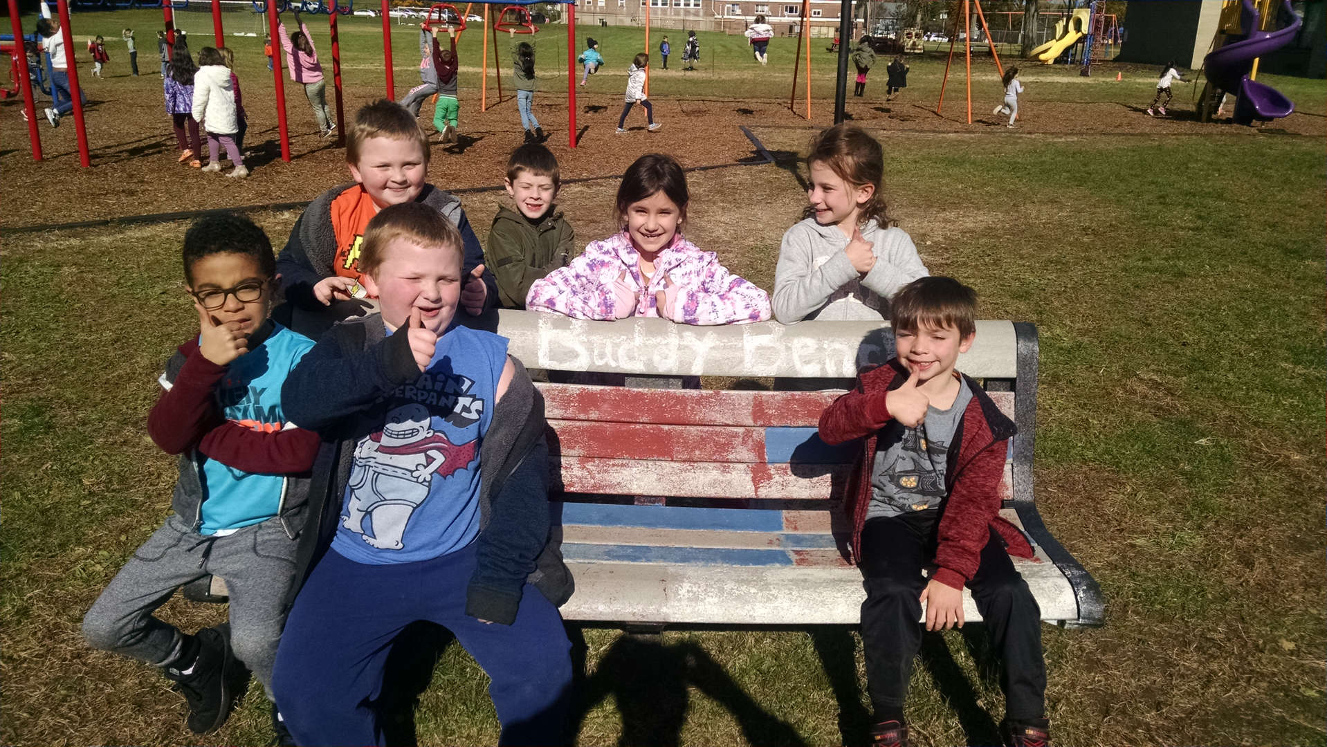 Second Graders showing how Compassion looks on one of our playground buddy benches.