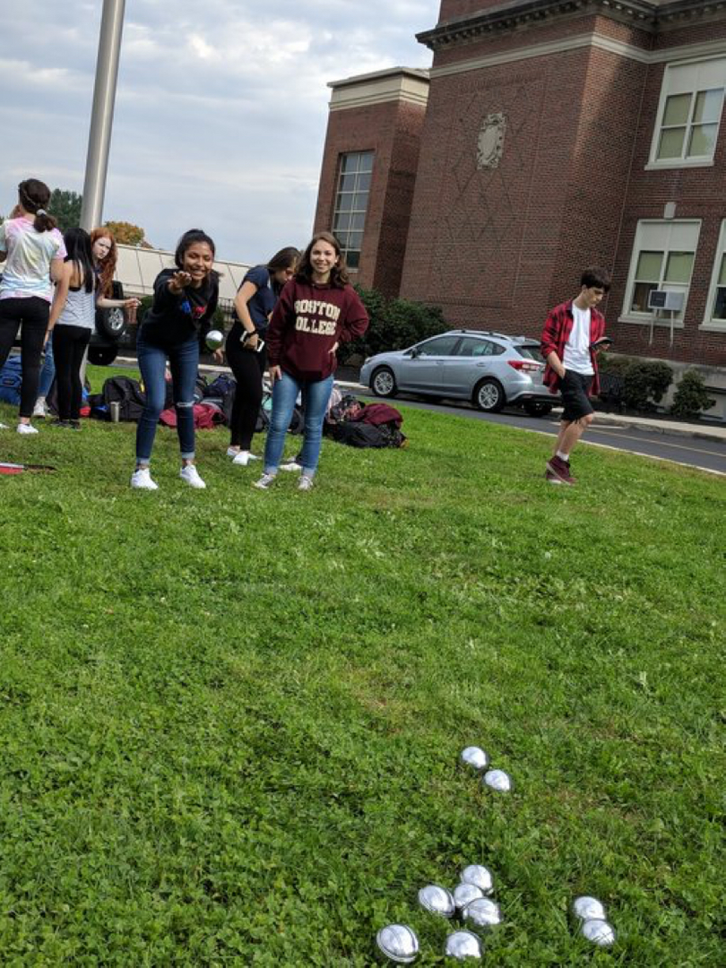 French Club students teaching Spanish and Italian-American Clubs how to play pétanque.