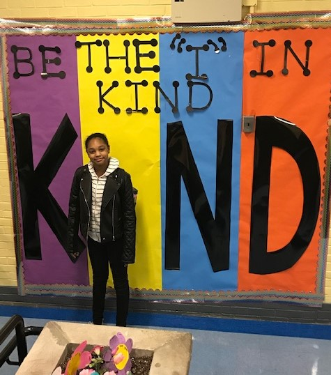 Student in front of Be Kind Poster