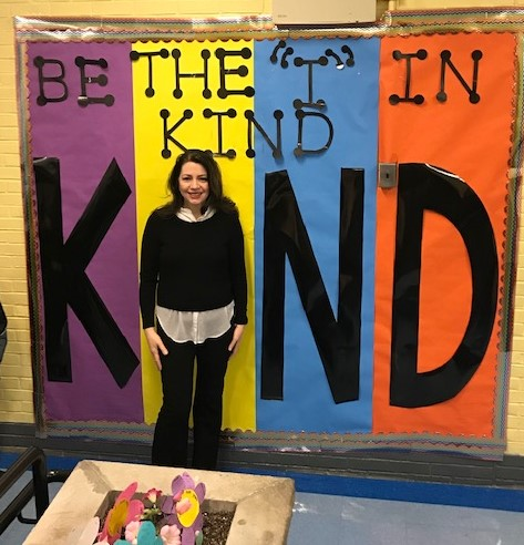 Staff Member in front of Be Kind Poster