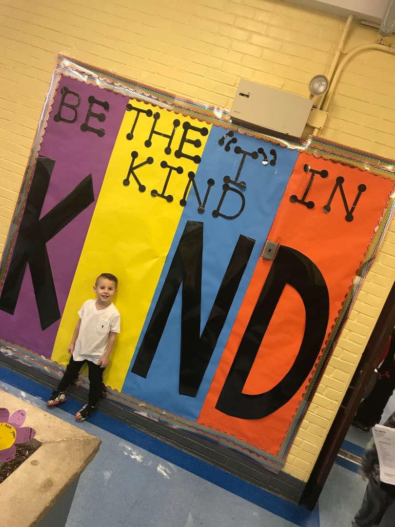 Kindergarten student in front of Be Kind Poster