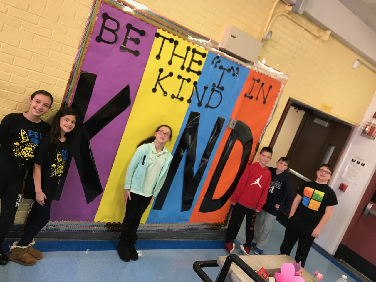 Children in front of Be Kind Poster