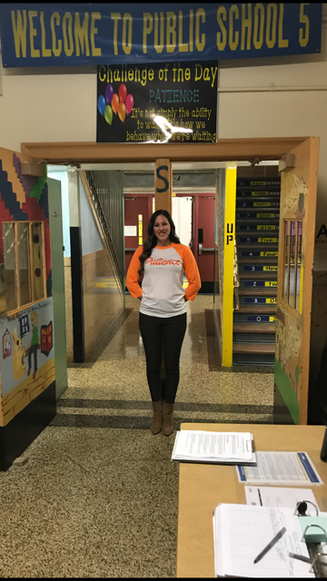 Mrs. Lanza in front of Challenge of the Day Poster