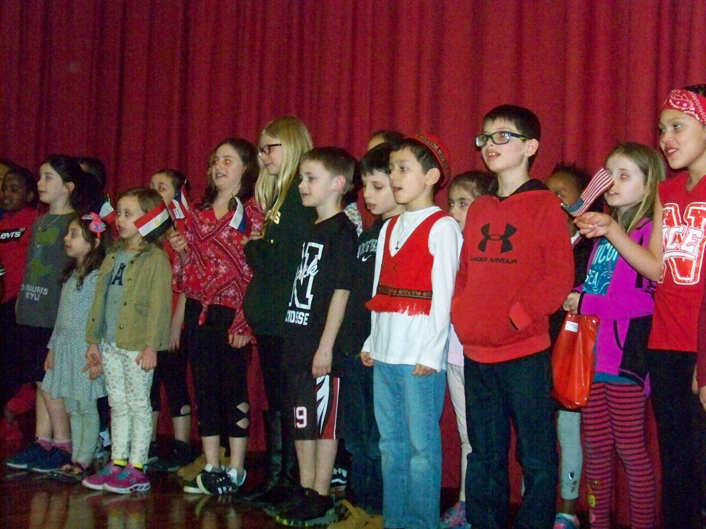 Students singing holding country flags