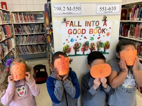 Reading Buddies welcome Fall with pumpkin faces.