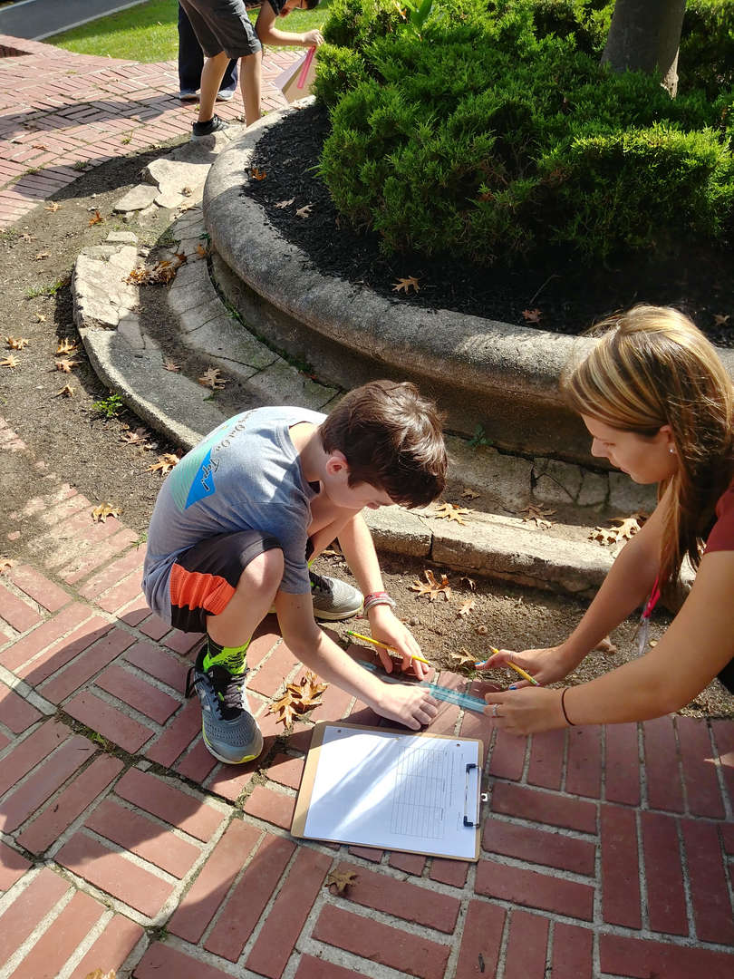 Science class takes learning outside the classroom to measure the various length of objects in nature.