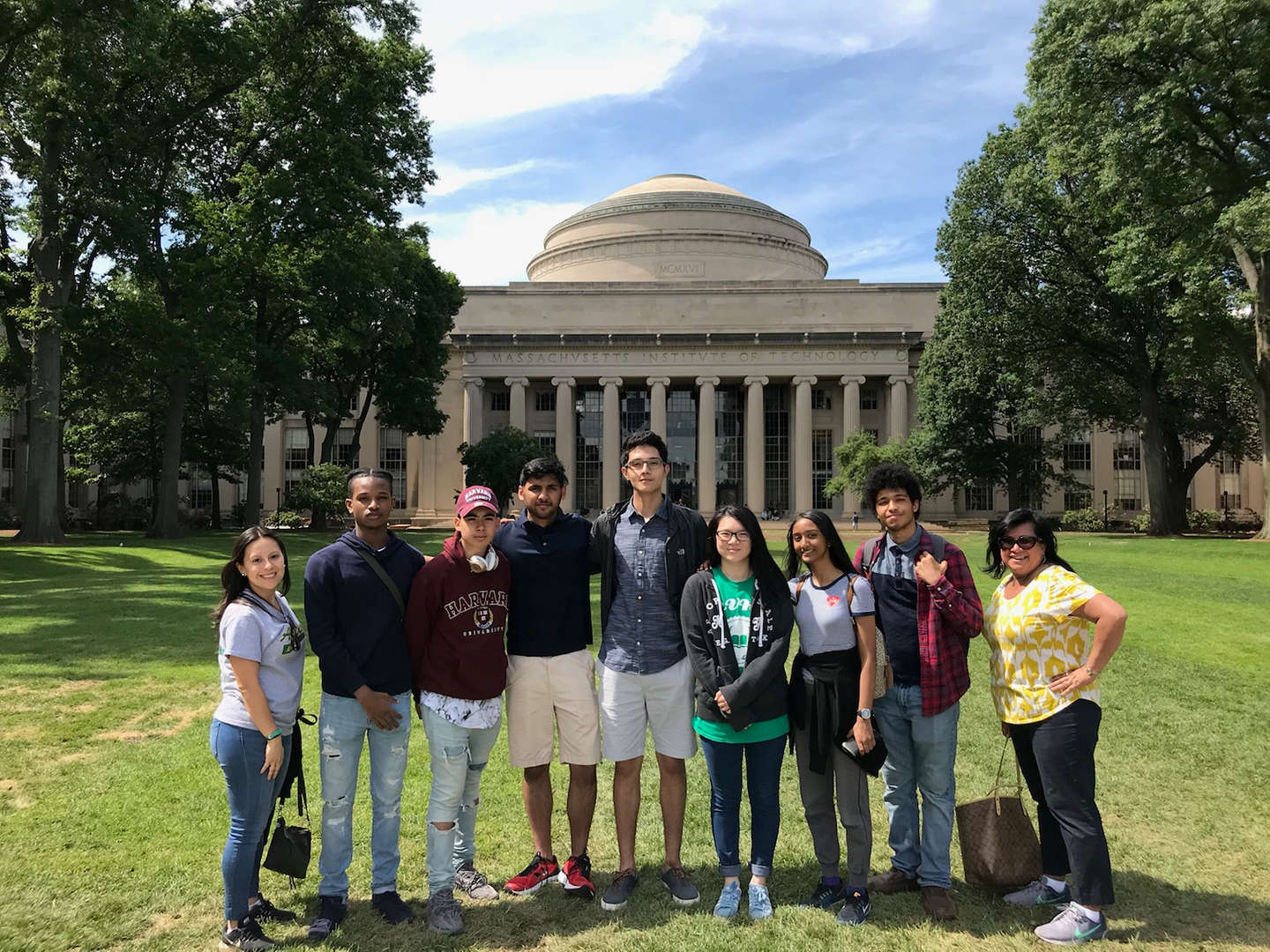 Seven students and two standing in front on a building at Harvard University