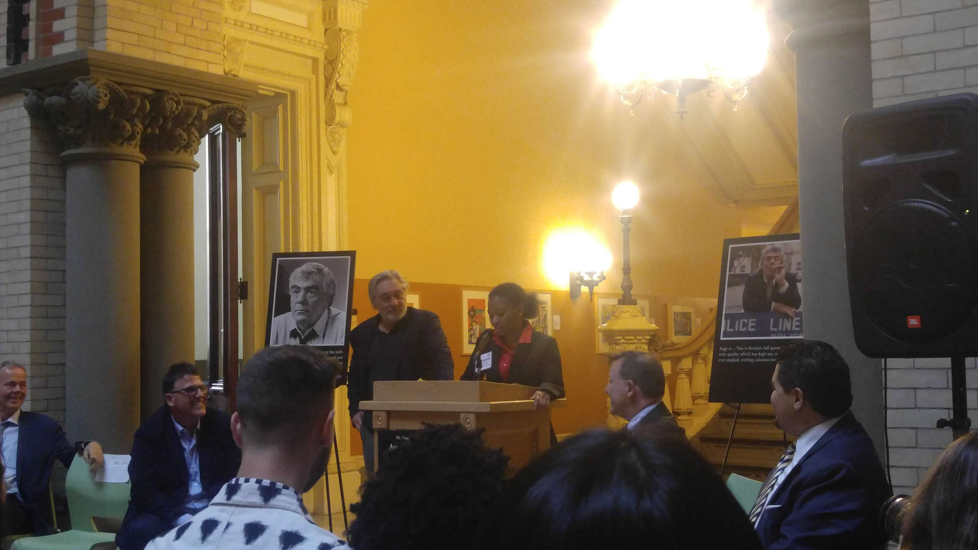 Senior Prestasia Aldridge speaking at a podium at the DOE's Tweed headquarters with Robert De Niro standing next to her