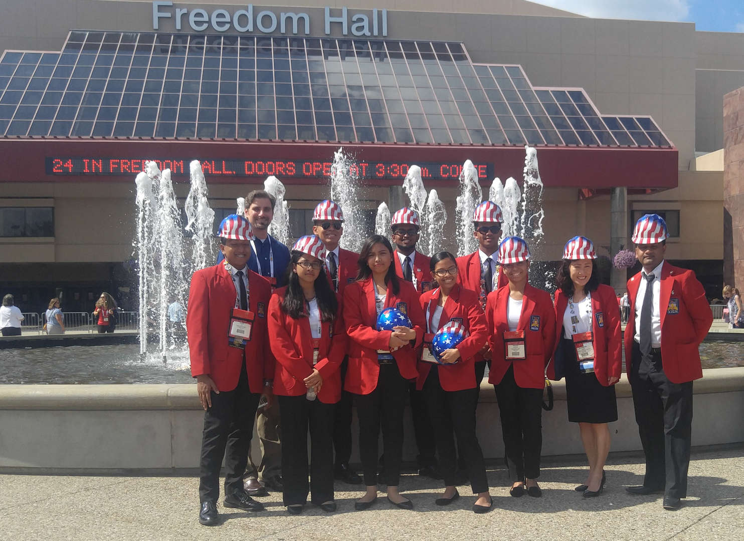 Eight students, two teachers and the principal standing in front of the water fountain at Freedom Hall at the Convention Center in Louisville, Kentucky.