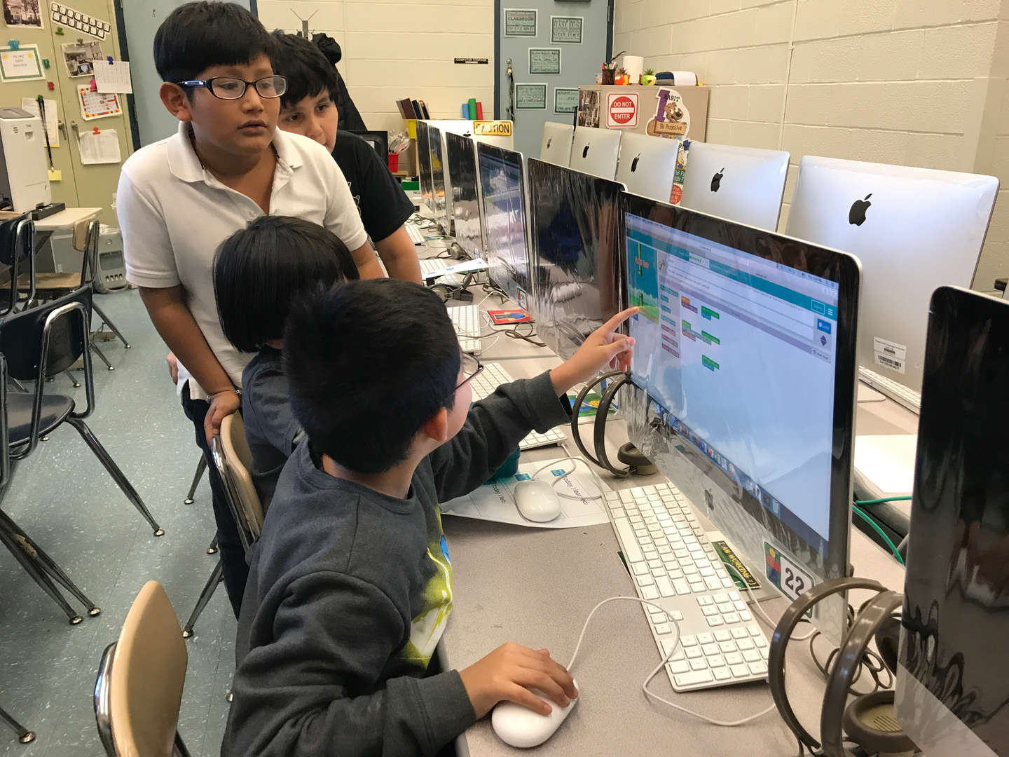 3 kids helping each other about the work on the computer