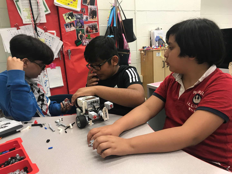 3 kids assembling lego robots