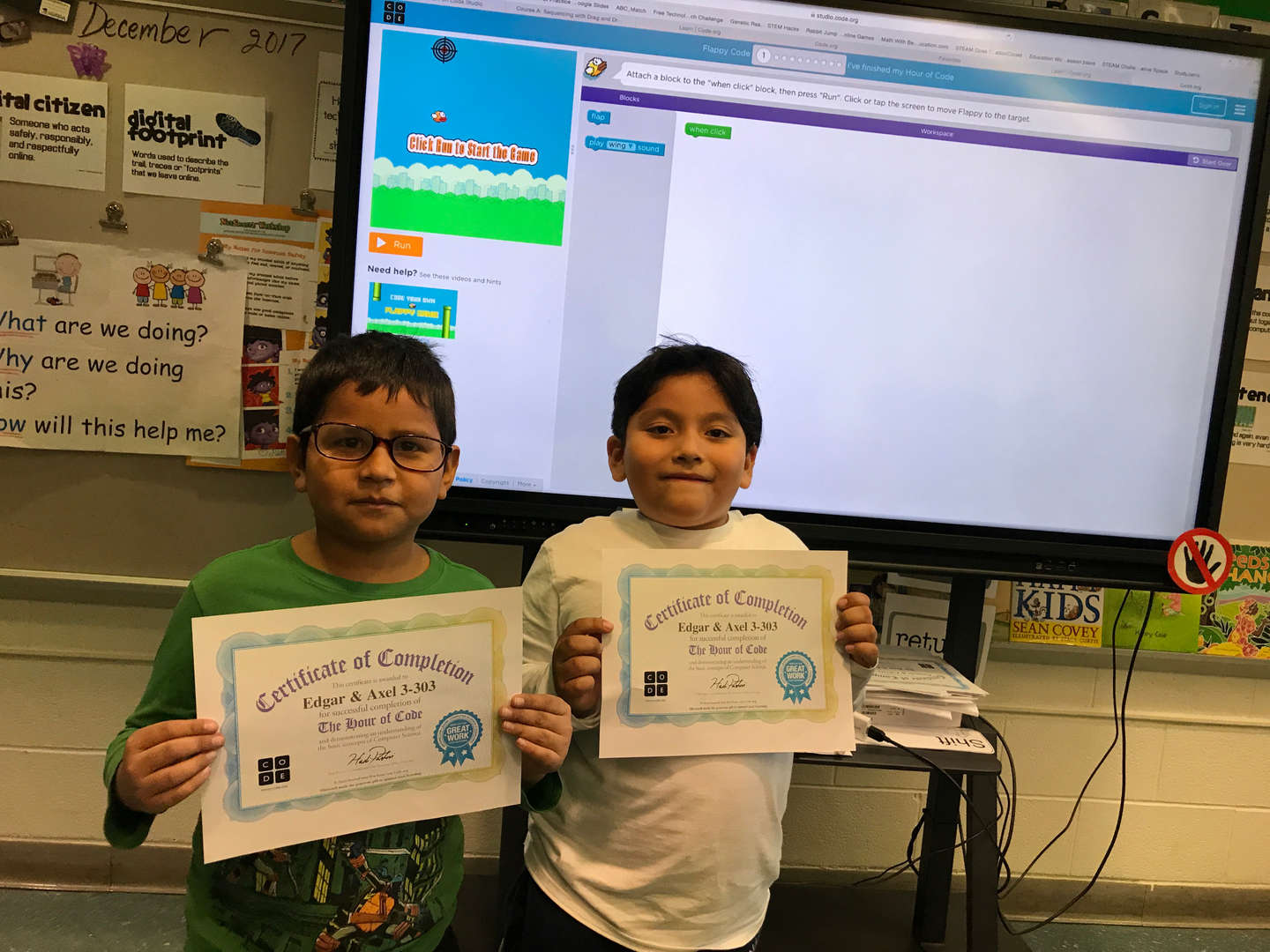 2 boys holding their certificates for coding