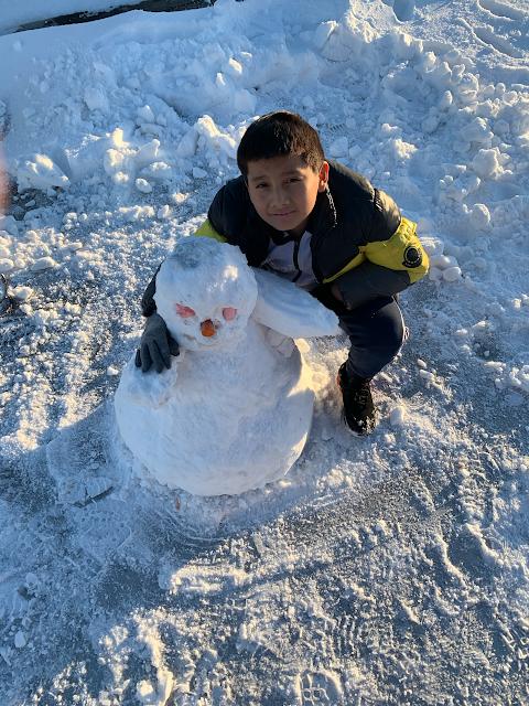 boy hugging a real snowman