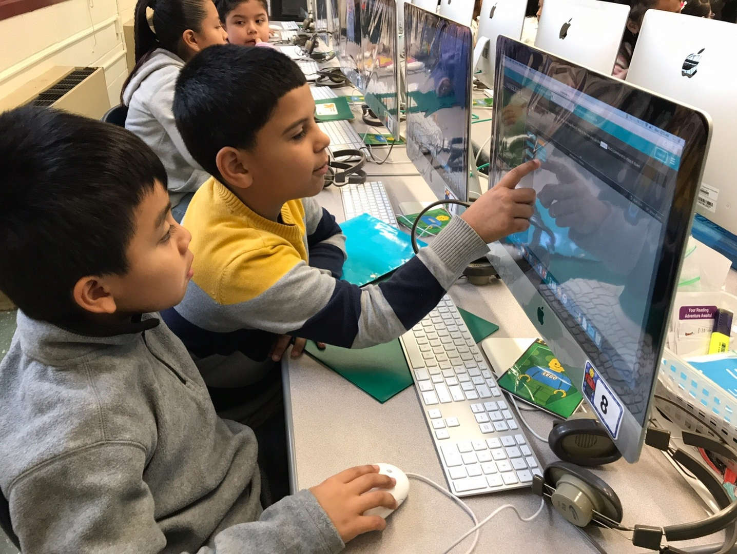 one boy showing and pointing on the computer screen to his classmate