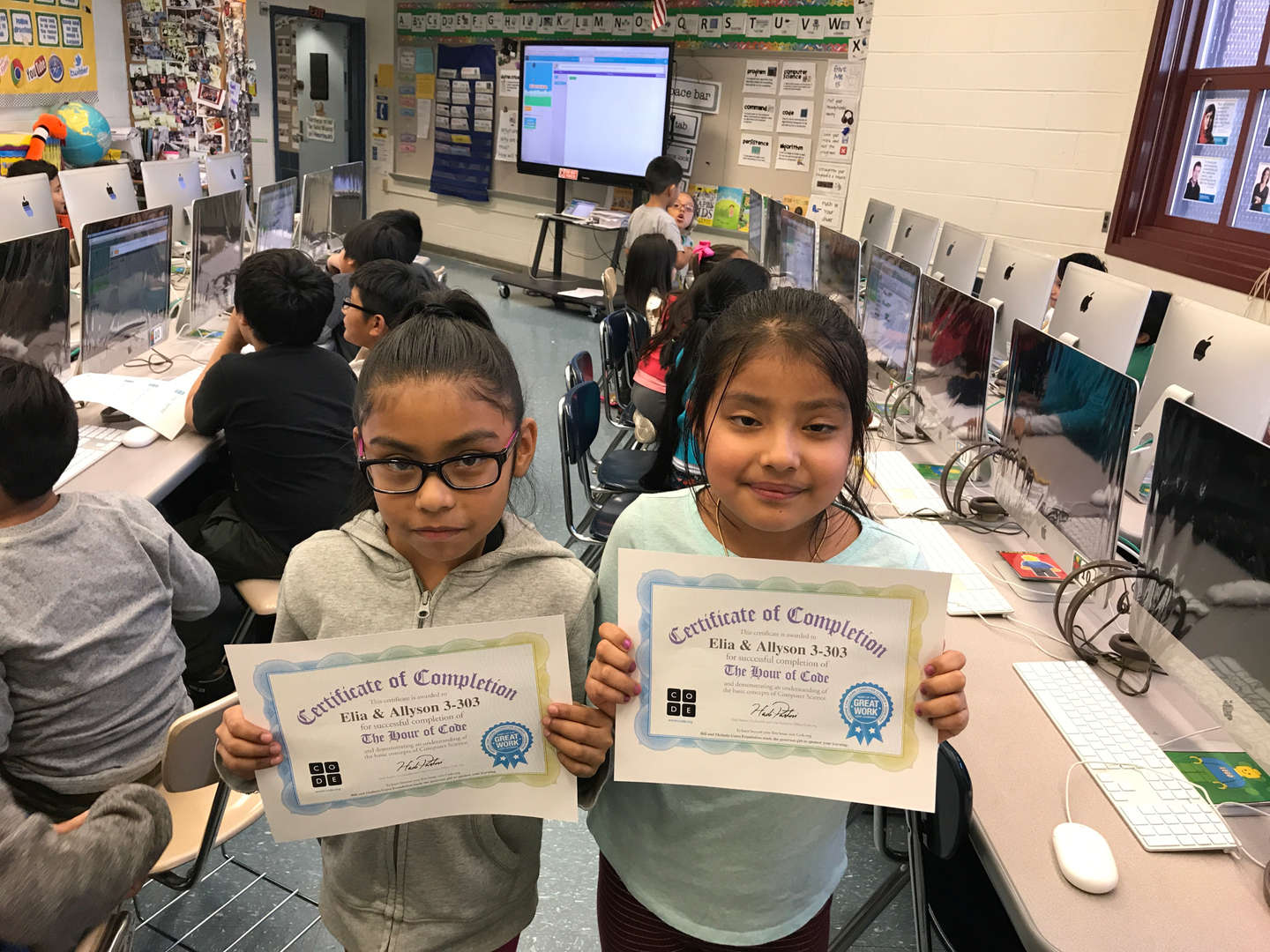 2 girls holding their hour of code certificates