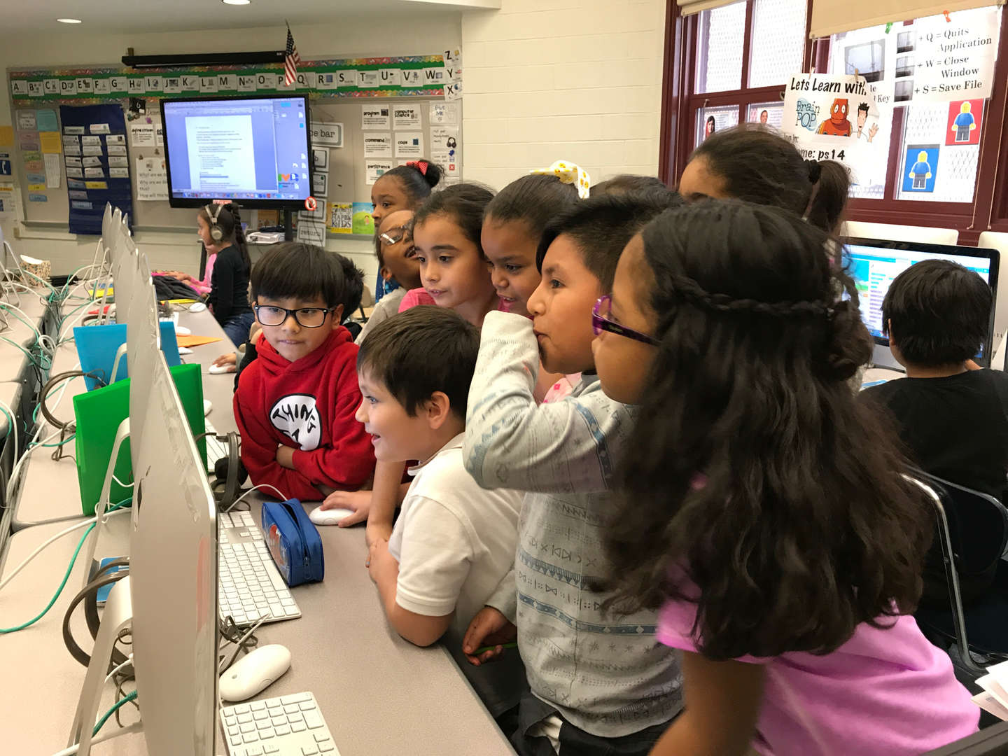a group of kids gathered around a computer station observing the screen