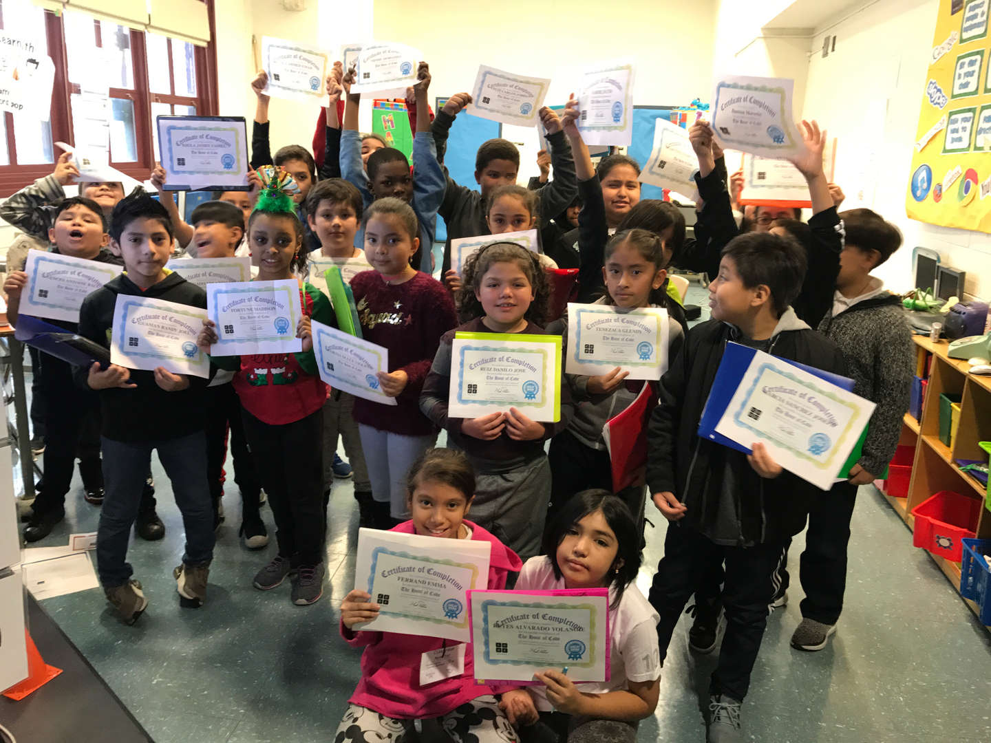kids in computer class holding their coding certificates