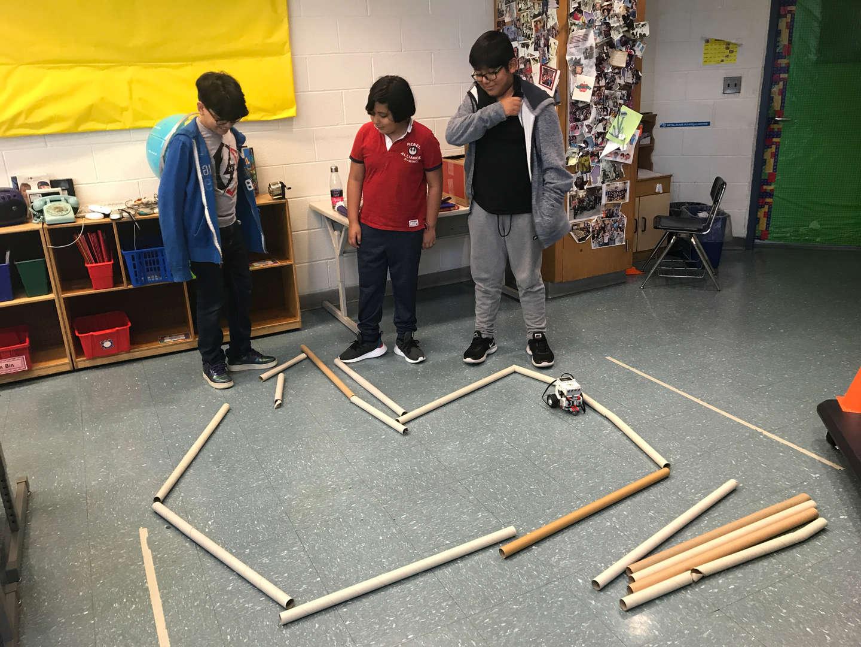 3. boys creating a path for Dash the robot