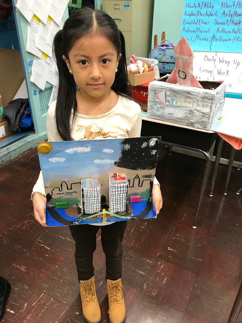 girl holding her project made out of recycle materials
