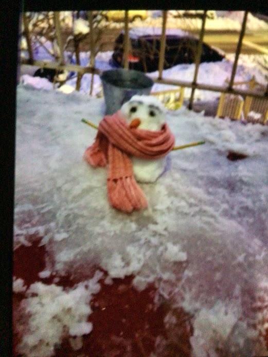 Real snowman wearing an orange scarf.