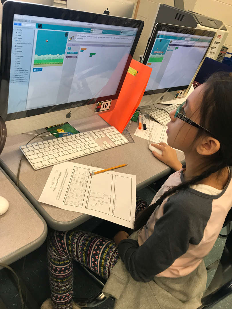 a girl working on her computer stations holding the mouse