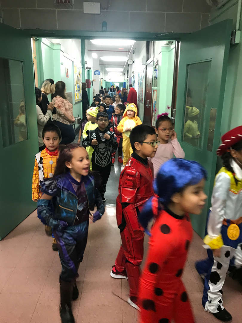students wearing their halloween costume walking in the school hallway
