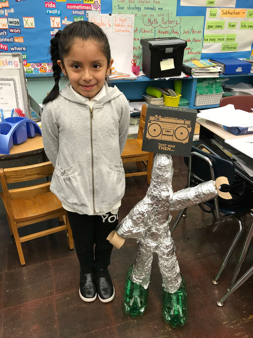 STUDENT WITH ALUMINUM FOIL ROBOT