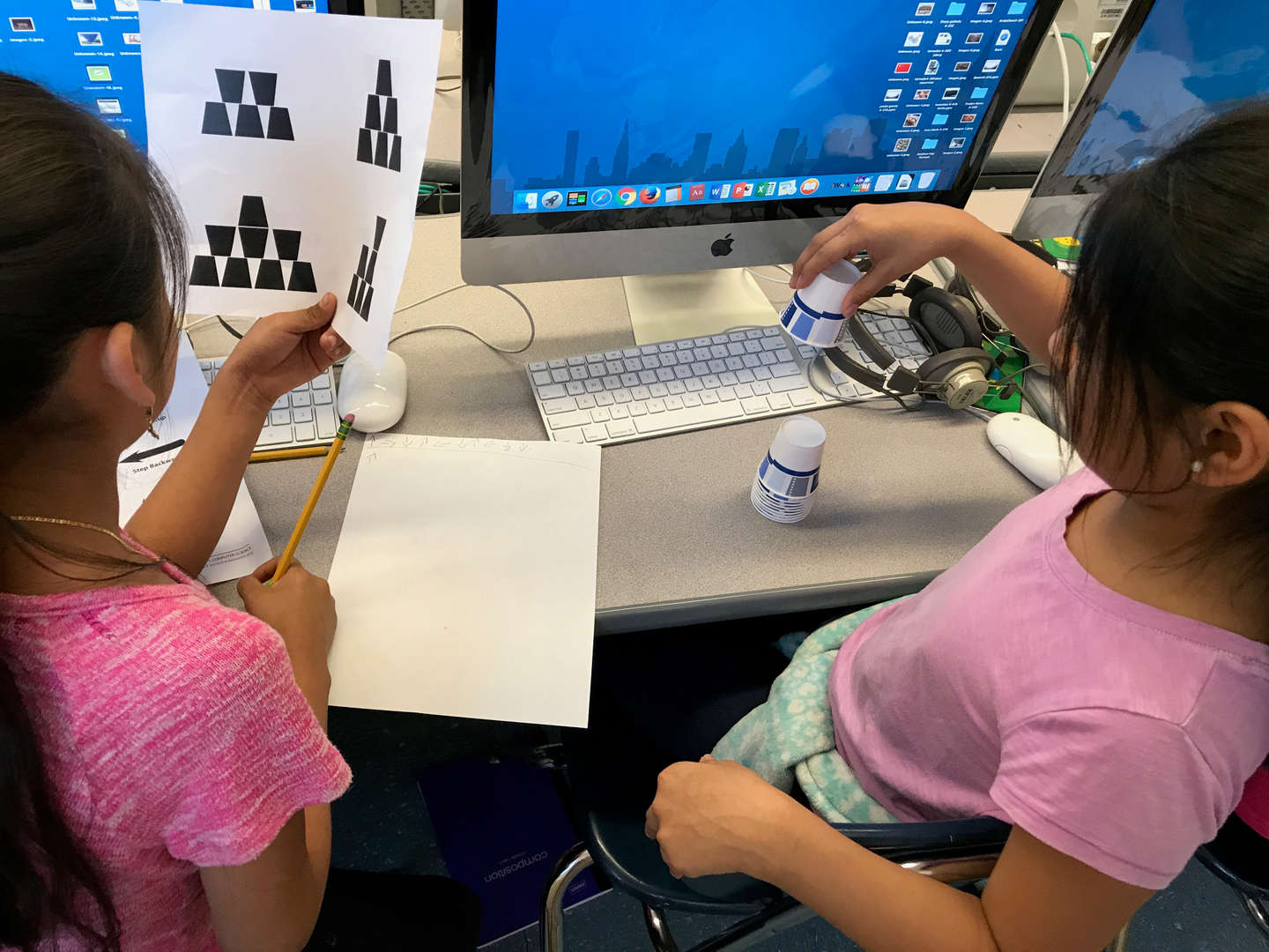 2 girls are sharing how to position the cups