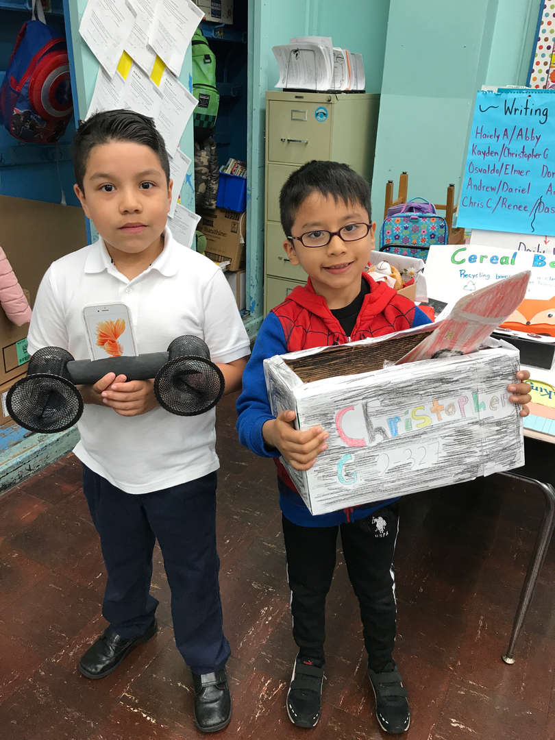 2 second graders holding their trash to treasure designs