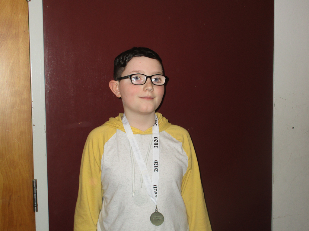 Champion, Quinlan, wears the Geography Bee medal