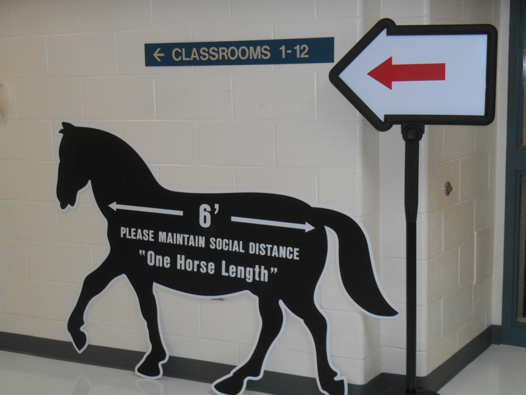 Social distance reminder sign shaped like a horse
