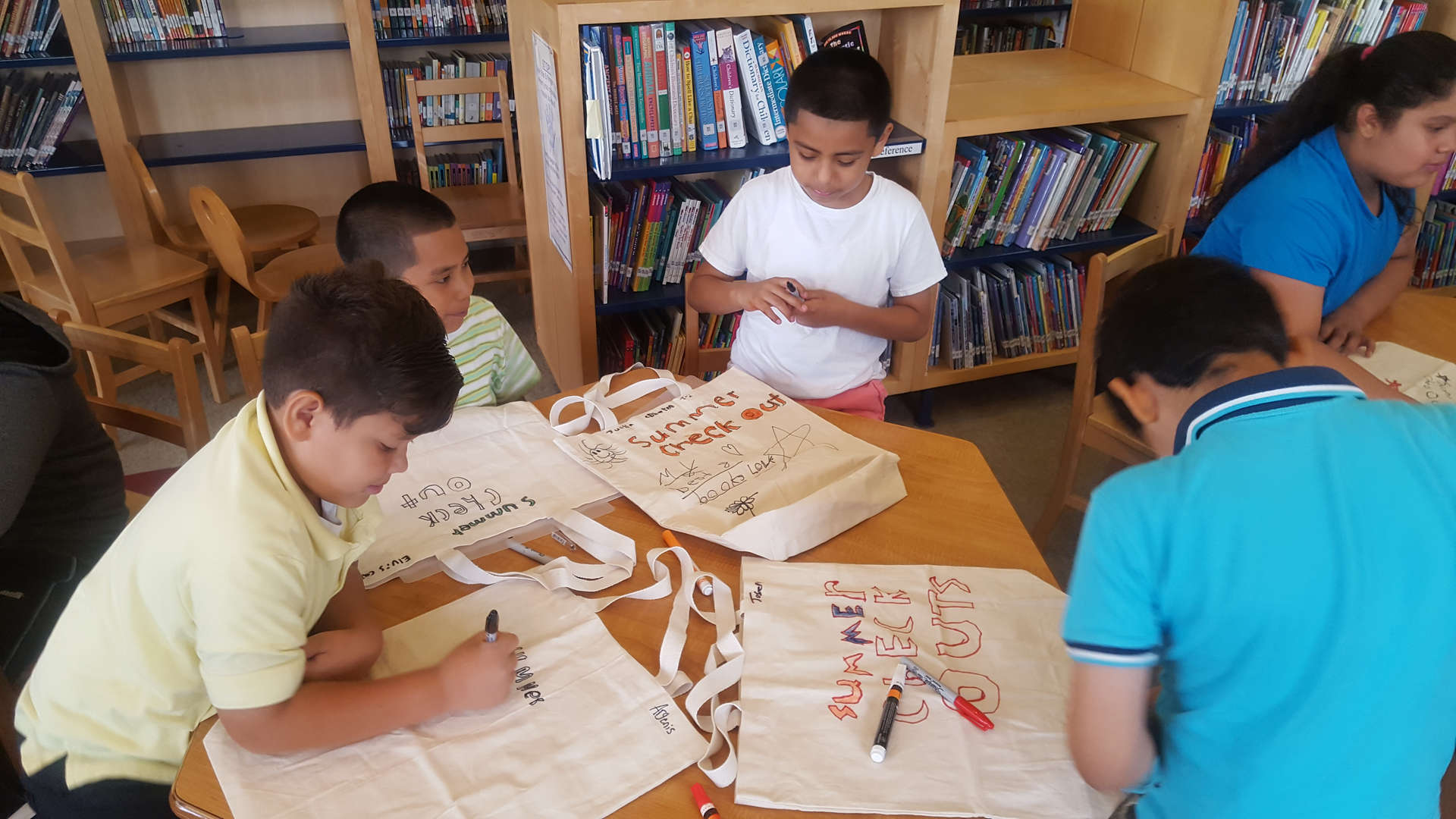 four students decorating tote bags in the library