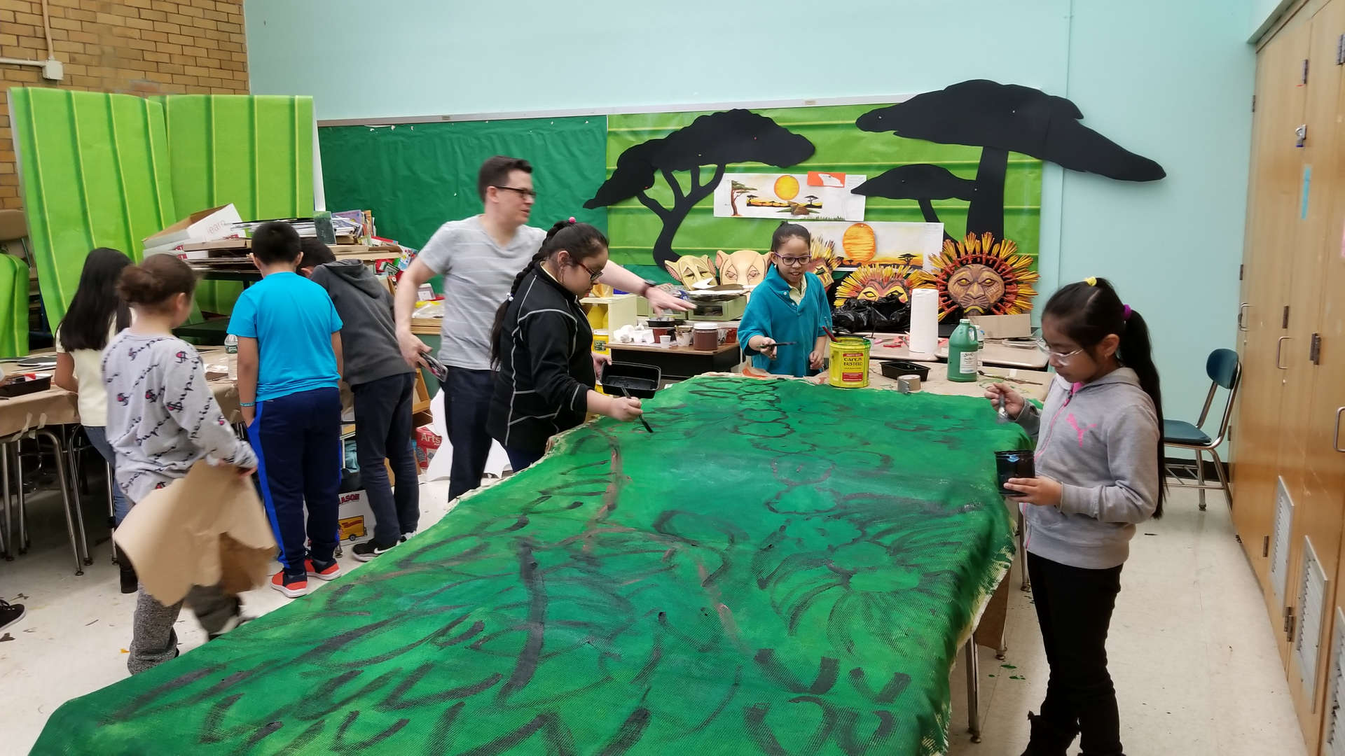 students painting backdrop for the Lion King Kids Musical