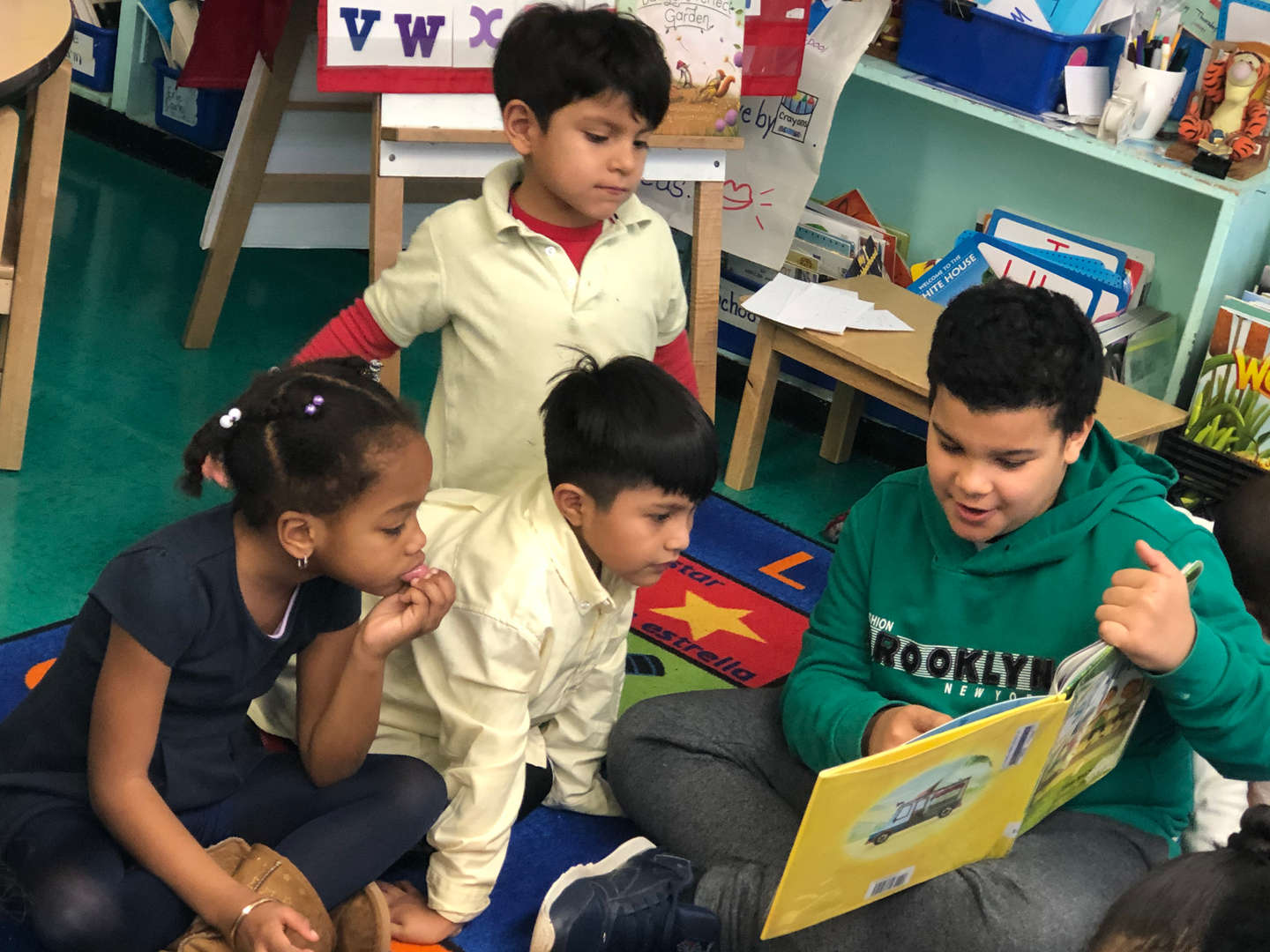 Upper grade student reading to lower grade