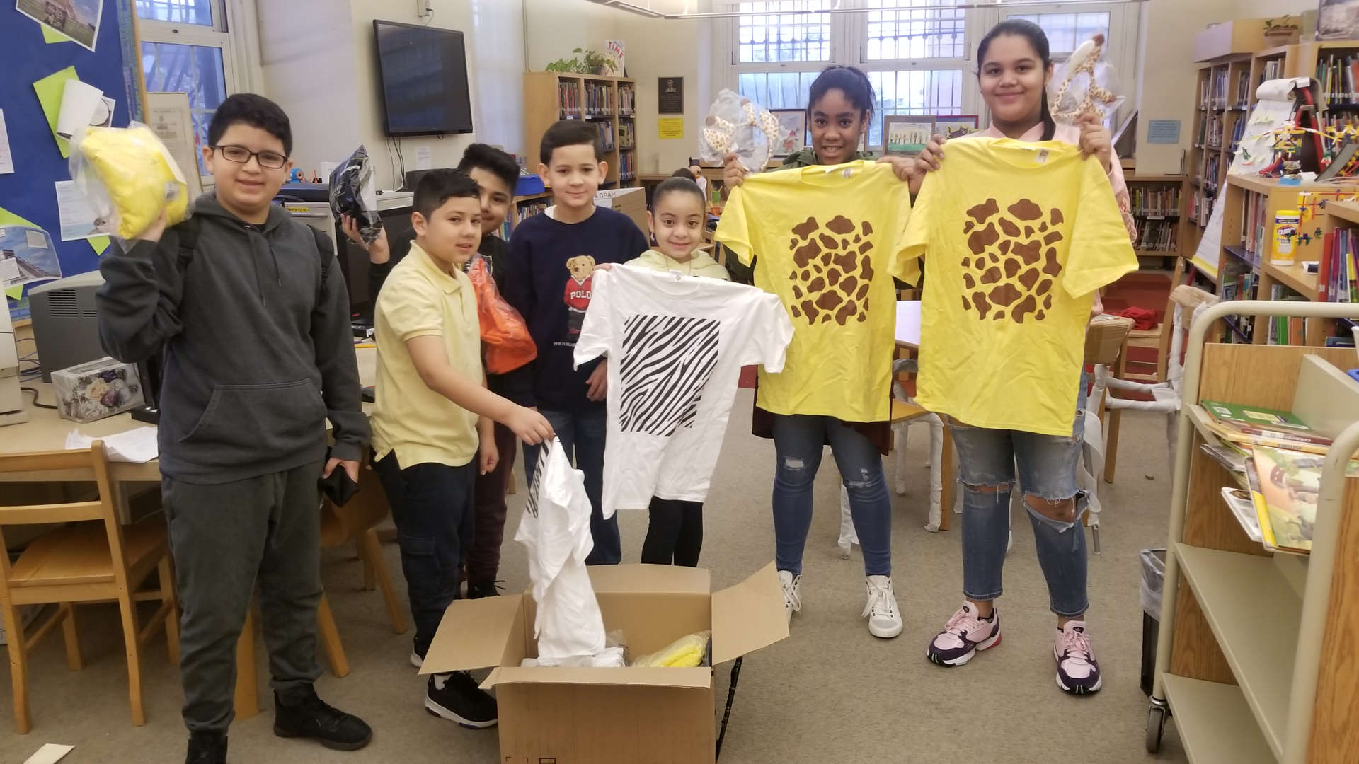 Students holding giraffe t shirts received from Donors Choose