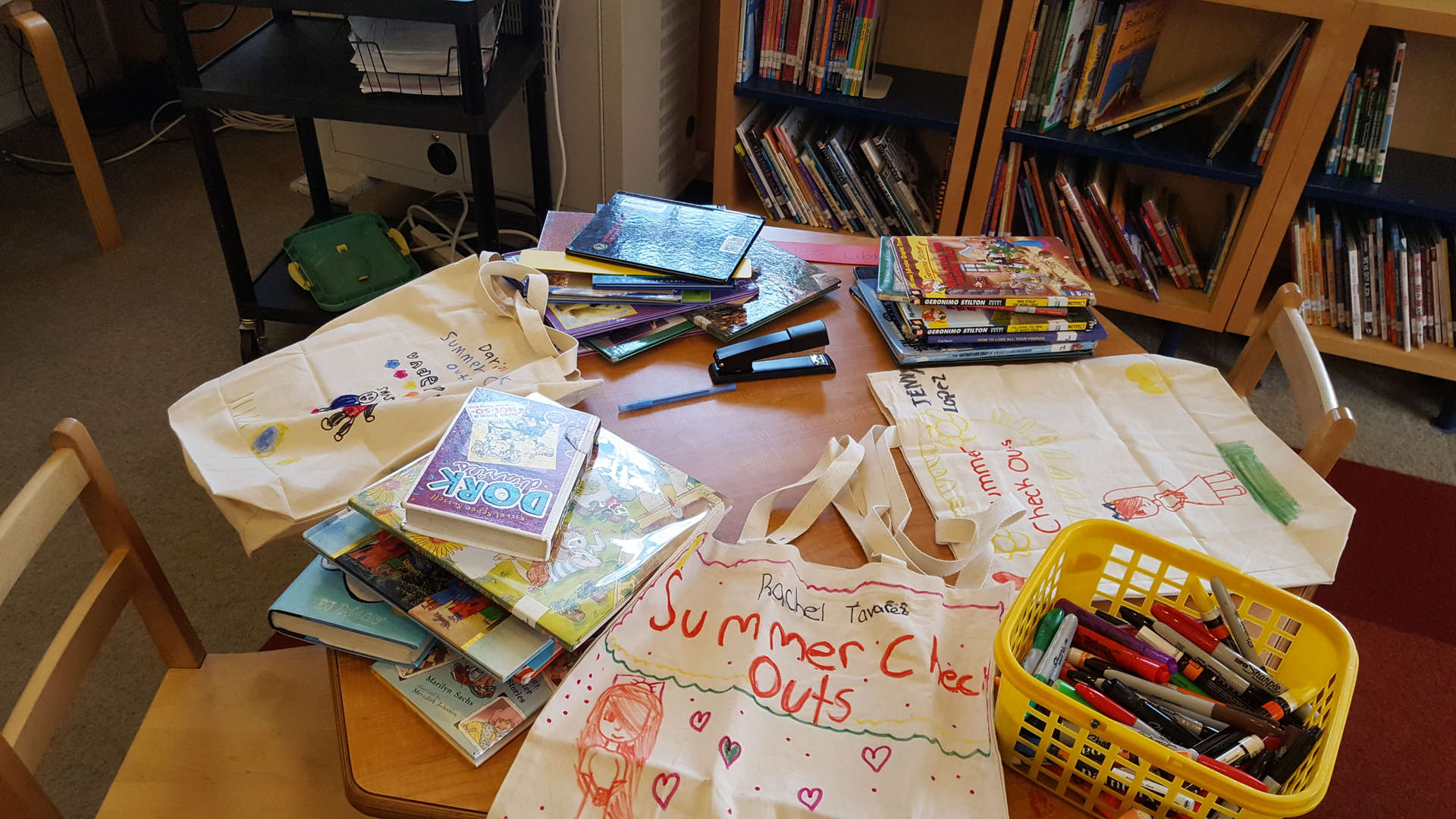 tote bags decorated by students and summer check out books