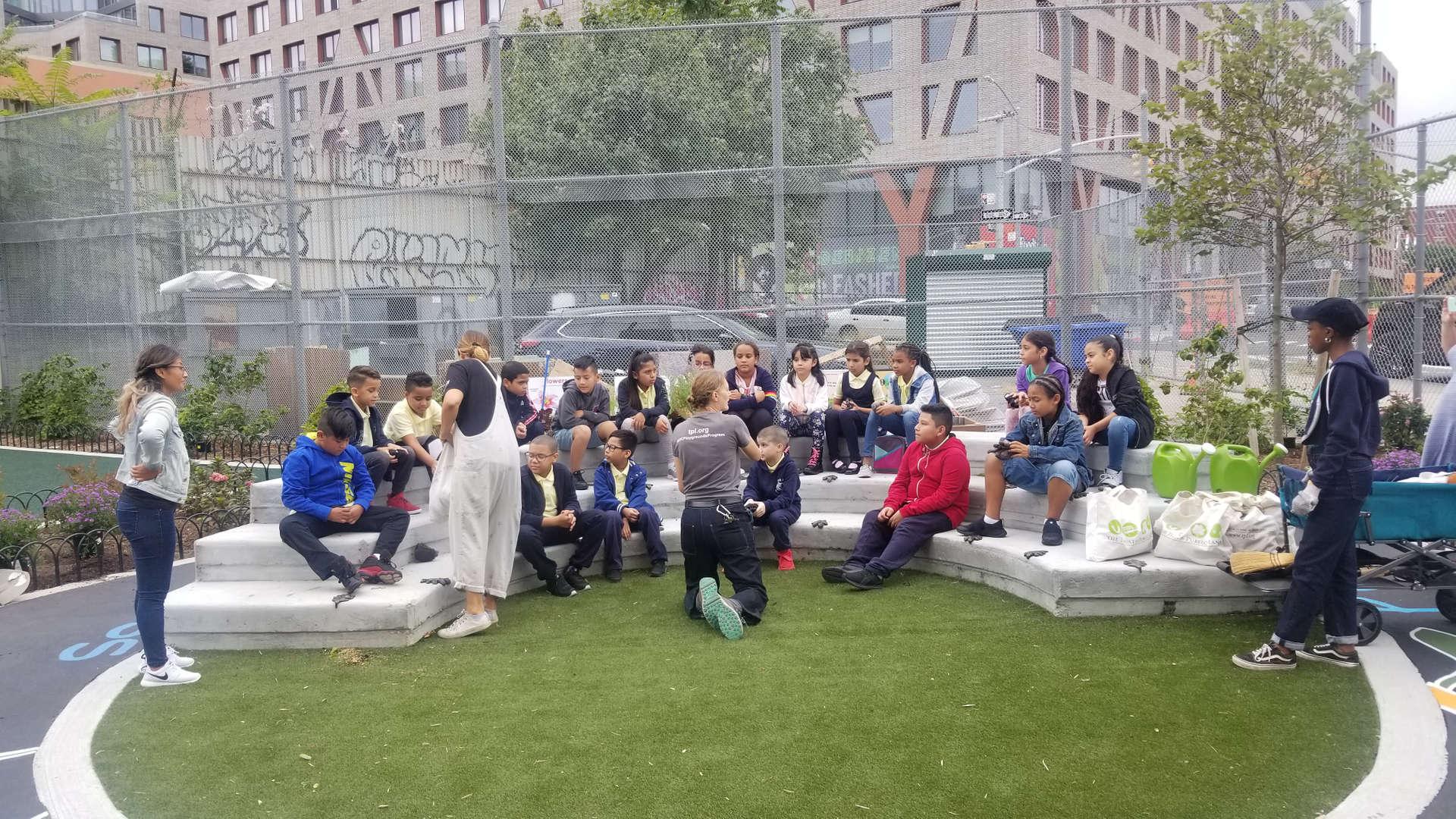 Students sitting on playground's amphitheater