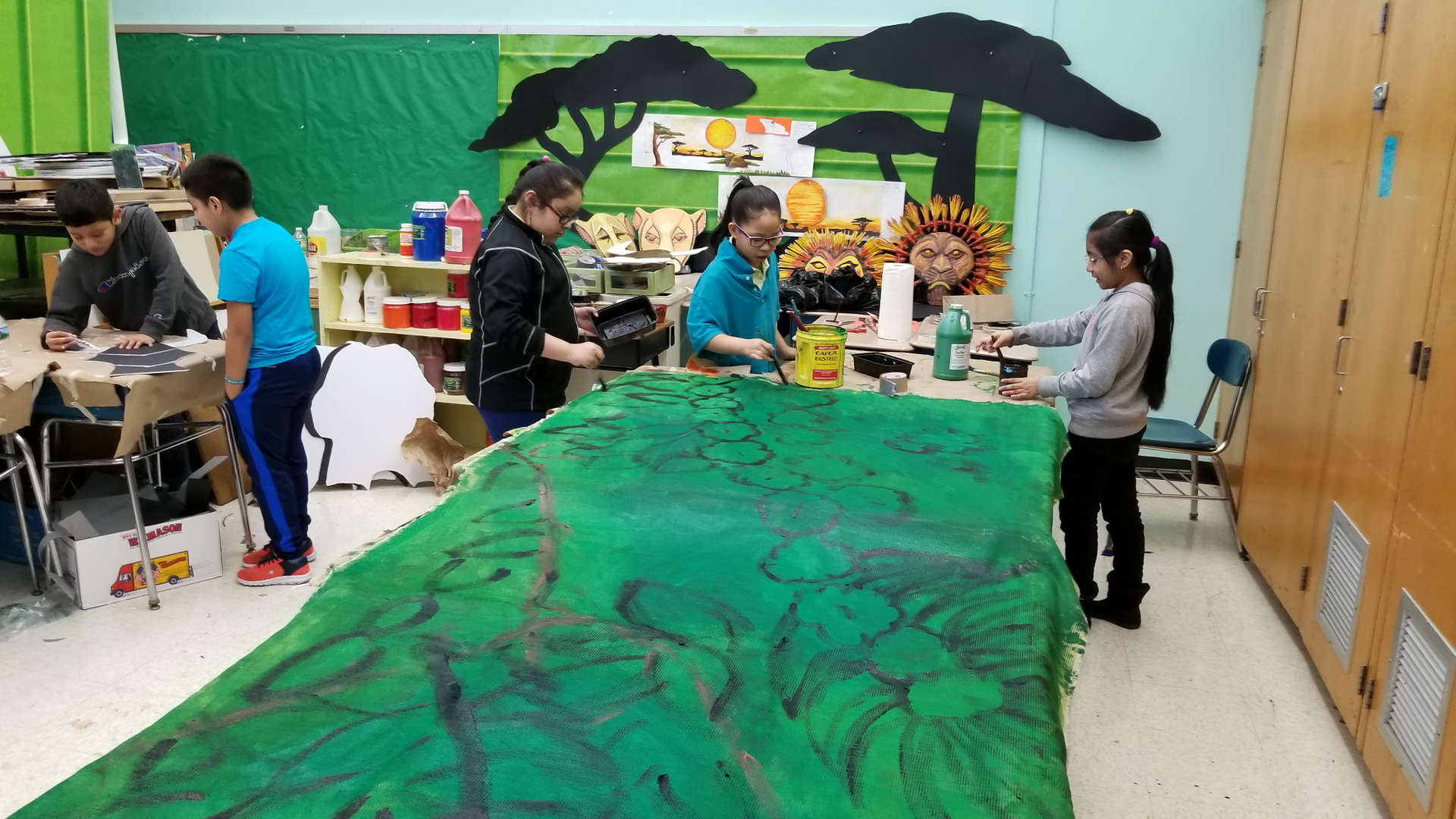 Back stage students creating the jungle scene backdrop for Lion King Kids Musical