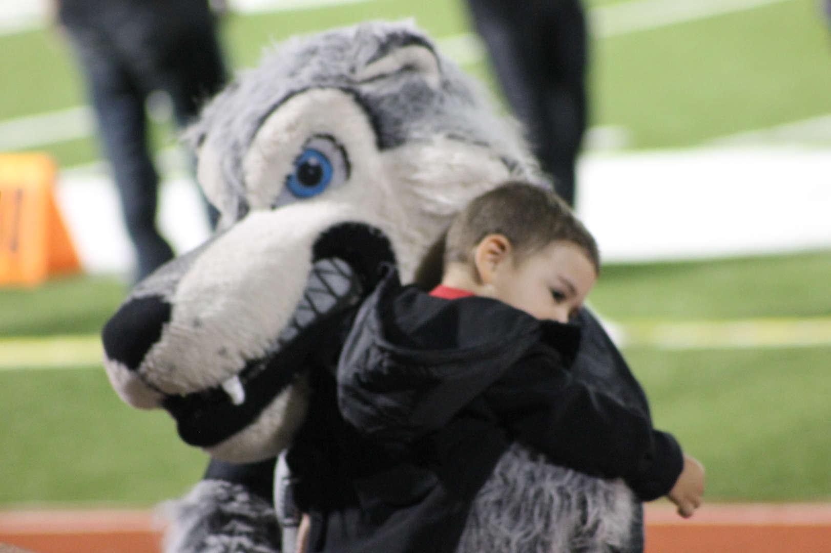 Lobo's mascot hugging a kid